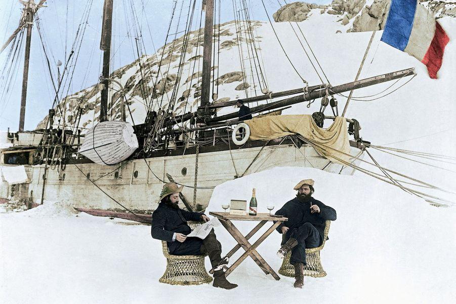 Bulles et lecture d'un vieil exemplaire du « Matin » pour Ernest Gourdon (à g.), géologue, et Paul Pléneau, photographe de l'expédition, devant le « Français », un trois-mâts de 32 mètres, sur l'île Wandel, en 1904.