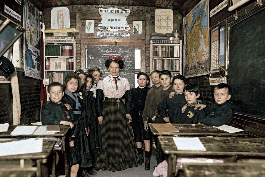 L'école de Jules Ferry, en 1900 : autour de la maîtresse et des écoliers, maximes morales, manuels recouverts de papier et une carte montrant notamment l'Algérie, département français depuis 1848.