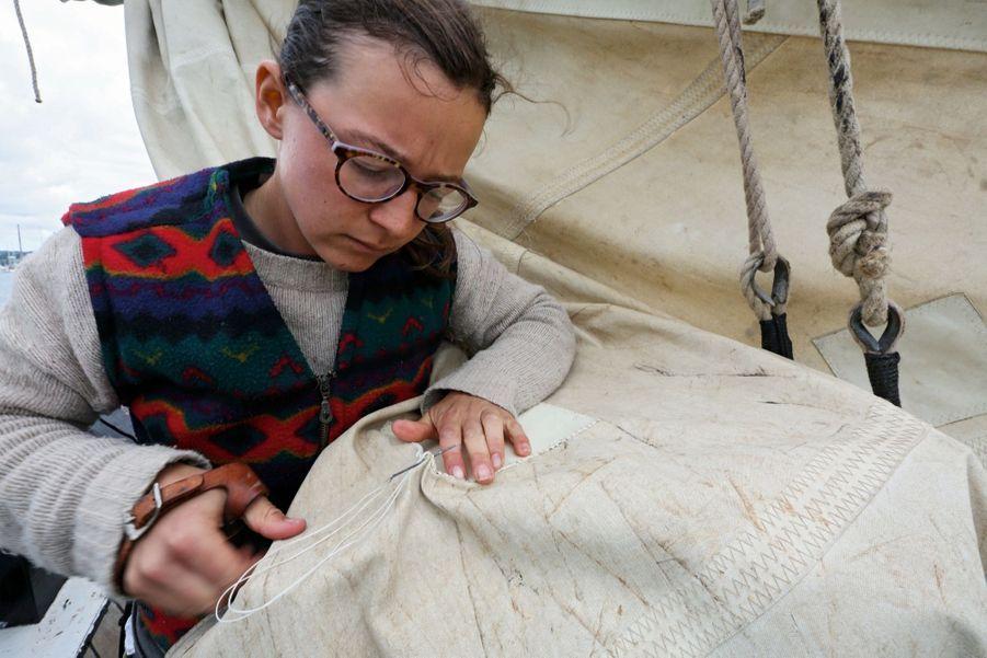 Travaux de couture pour Rachel qui met une pièce sur une voile.