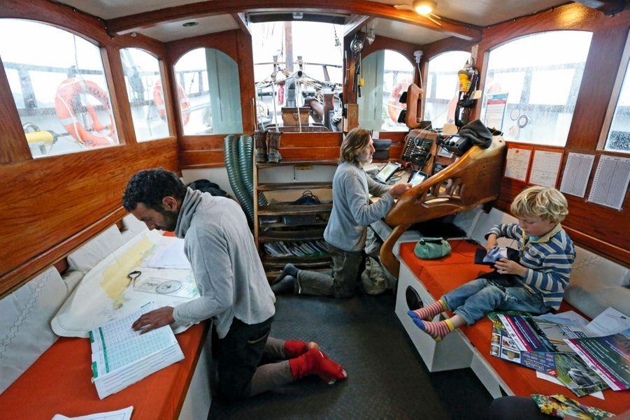 Erwan, le Français (à g.), prépare la route. Marcus, le capitaine anglais, remplit le livre de bord. Son fils Malachi, 5 ans, vit sur le bateau depuis sa naissance.