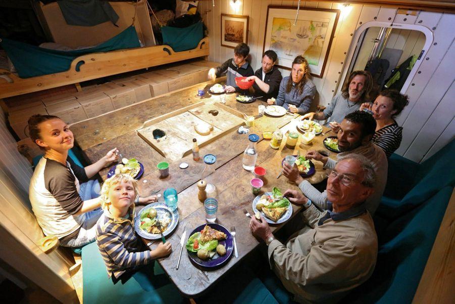 Dans le carré à l'heure du dîner. De g. à dr. : Rachel, une équipière, Malachi, Tony, un passager, Erwan, Freya, Marcus, Noémie, une bénévole, James et Guy, deux autres passagers anglais.