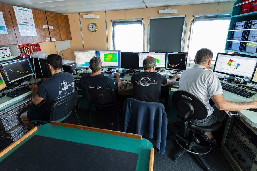 «Seconde phase de la nouvelle campagne de recherche du sous-marin La Minerve, disparu le 27 janvier 1968 au large de Toulon. Du 3 au 13 juillet 2019, l'Antea, navire de recherche pluridisciplinaire de l'Institut de Recherche pour le Développement (IRD), met en œuvre un drone sous-marin AsterX de l'IFREMER chargé de rechercher des anomalies sur le fond marin, à environ 2300 mètres sous la surface de l'eau.Àl'image, le personnel embarqué du SHOM analyse les données récoltées la veille par le drone AsterX.»