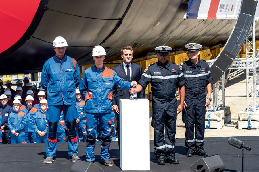 Le lancement symbolique : de g. à dr., Olivier Folliot, ouvrier de Naval Group, l'apprenti Léo Demazeau, Emmanuel Macron, le second-maître Kévin et le commandant du « Suffren », le capitaine de frégate Axel Roche.