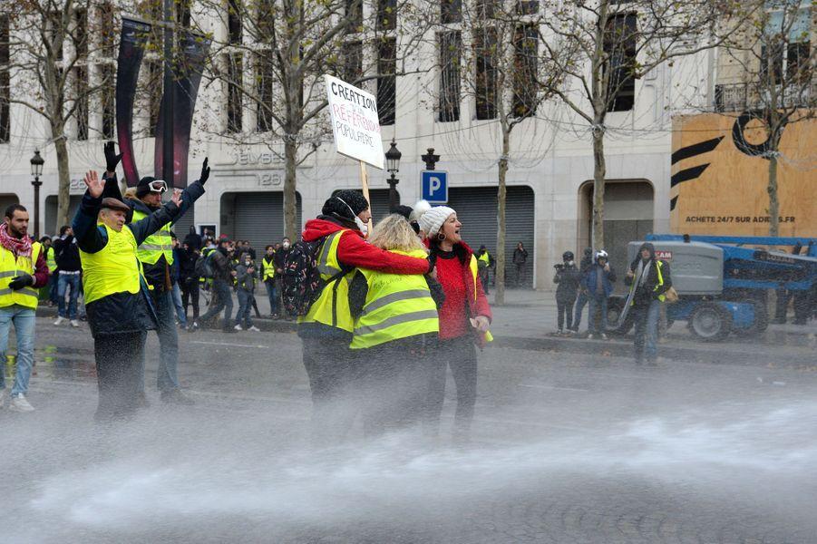 Des «gilets jaunes» font face aux jets d'eau, samedi sur les Champs-Elysées.