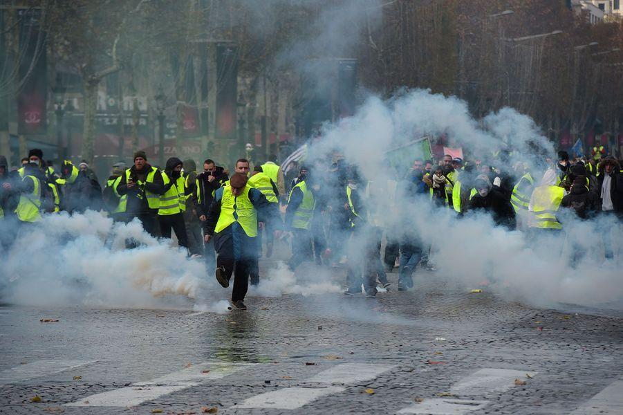 Des «gilets jaunes» dégagent des grenades lacrymogènes sur les Champs-Elysées, samedi.