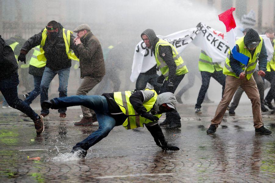 Des gilets jaunes visés par le canon à eau de la police, samedi sur les Champs-Elysées.