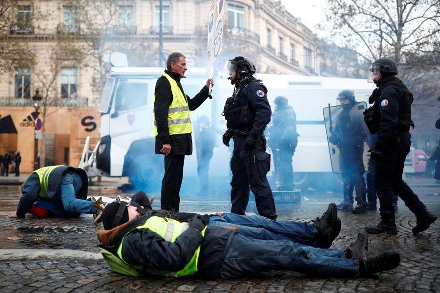 Un gilet jaune s'explique avec un policier, samedi sur les Champs-Elysées.