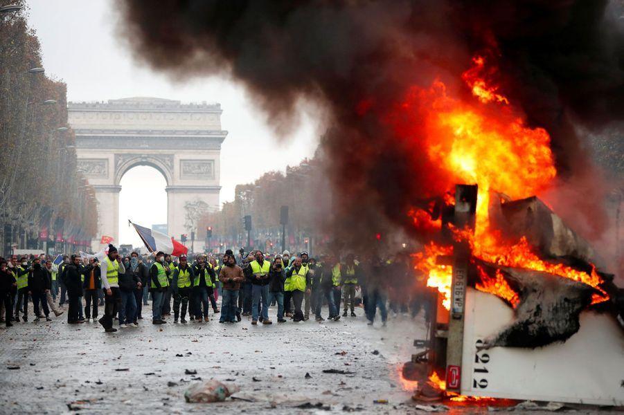 Une barricade de gilets jaunes en flammes, samedi sur les Champs-Elysées.
