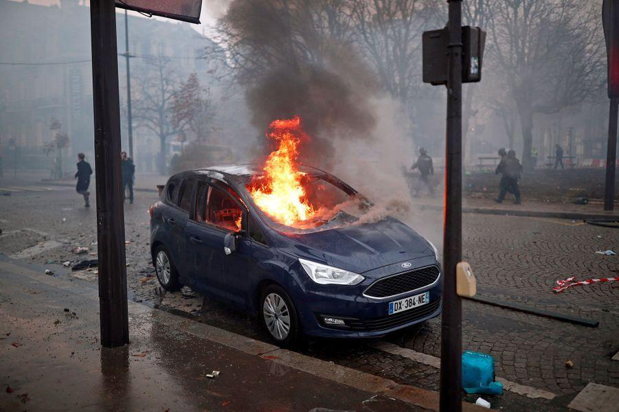 Une voiture en flammes sur les Champs-Elysées à Paris, samedi.