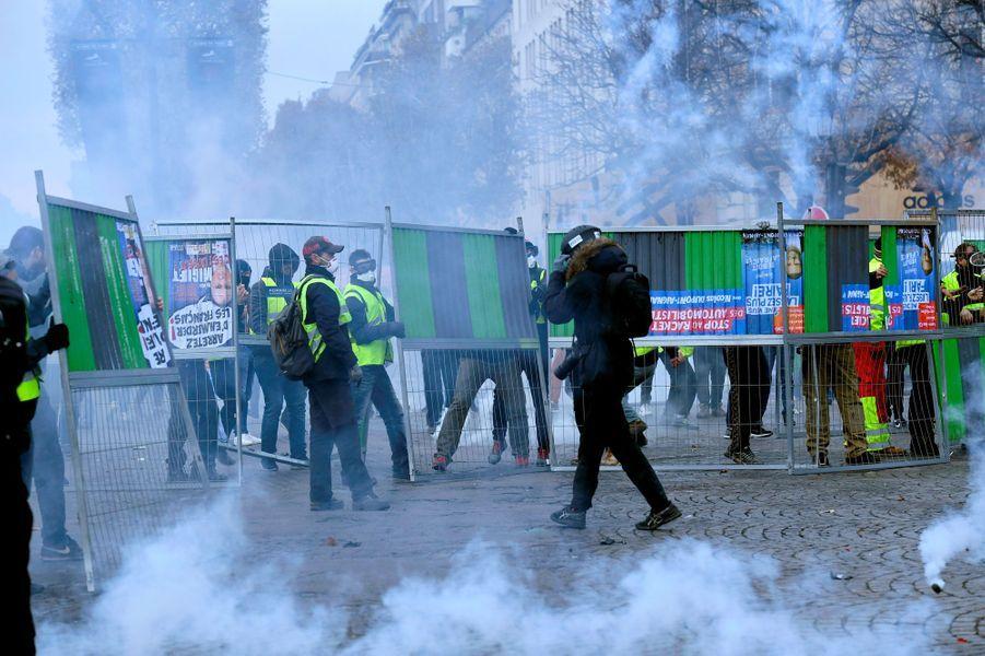 Face-à-face dans un brouillard de gaz lacrymogène sur les Champs-Elysées, samedi.