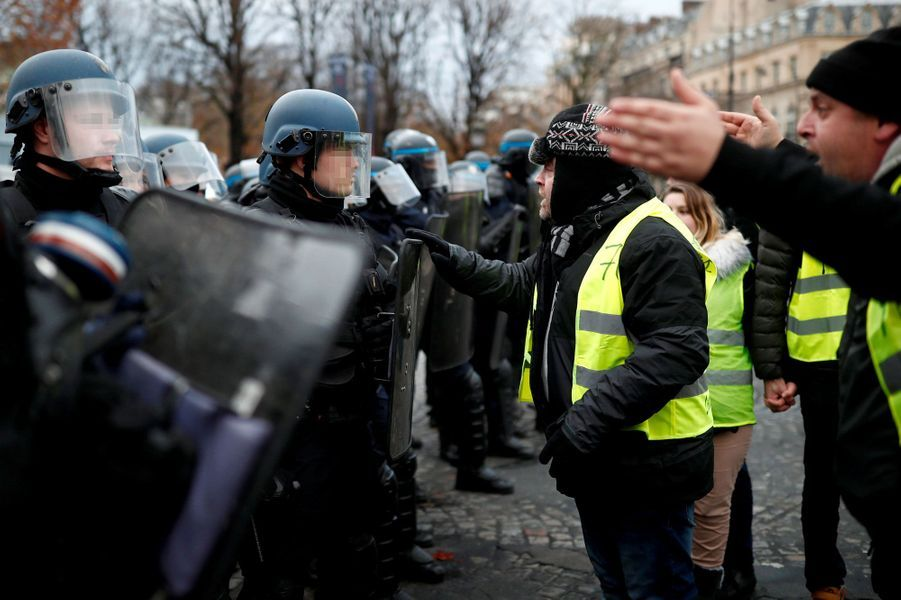 Des manifestants face aux policiers, samedi, sur les Champs-Elysées.