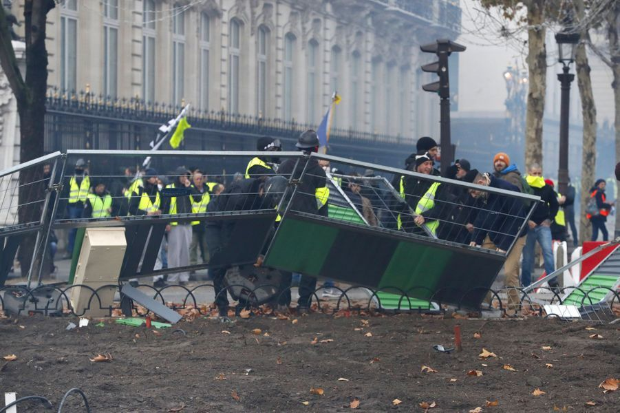 Des manifestants s'emparent du mobilier urbain sur les Champs-Elysées, samedi.