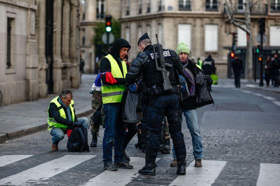 Des «gilets jaunes» contrôlés par un gendarme aux abords des Champs-Elysées, samedi matin.