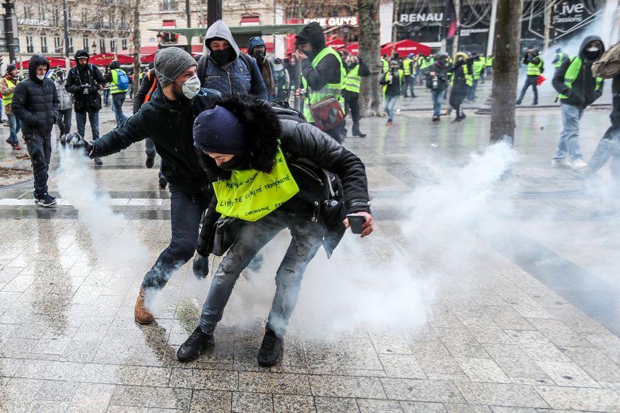 Des «gilets jaunes» parmi les gaz lacrymogènes, samedi sur les Champs-Elysées.