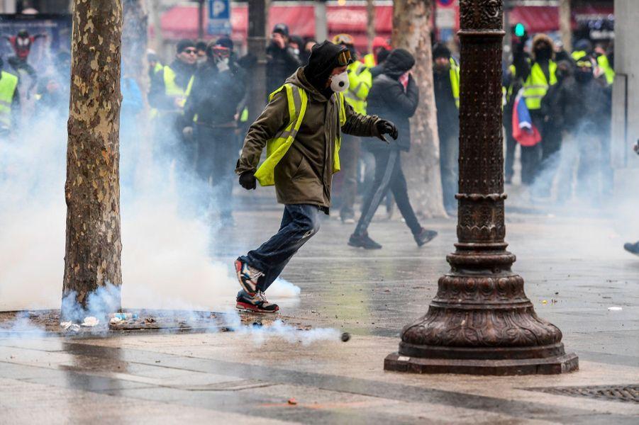 Un «gilet jaune» parmi les gaz lacrymogènes, samedi sur les Champs-Elysées.