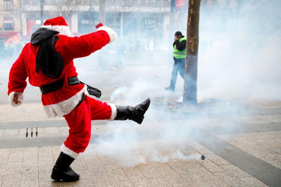 Un manifestant déguisé en père Noël repousse une grenade lacrymogène, samedi sur les Champs-Elysées.