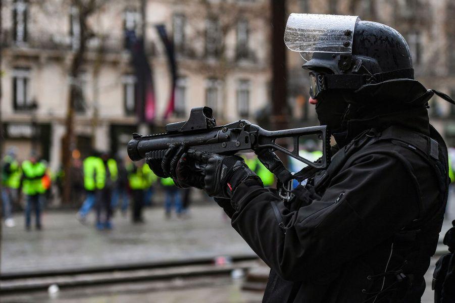 Un policier avec un lanceur de balles de défense sur les Champs-Elysées, samedi.