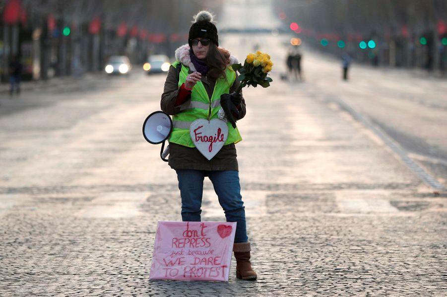 Une manifestante portant un gilet jaune sur les Champs-Elysées, samedi matin.