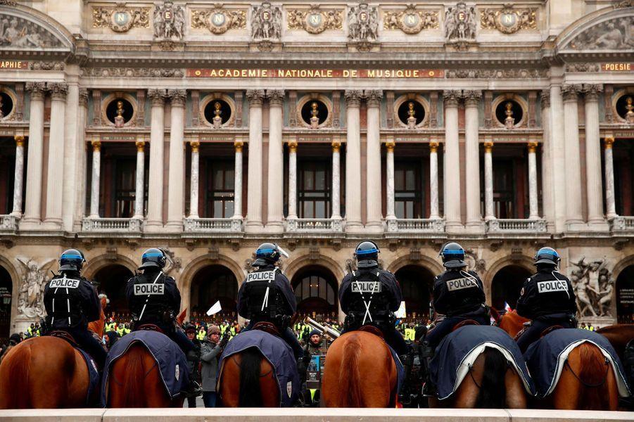 Une unité équestre de la police encadre les manifestants devant l'Opéra, à Paris, samedi.