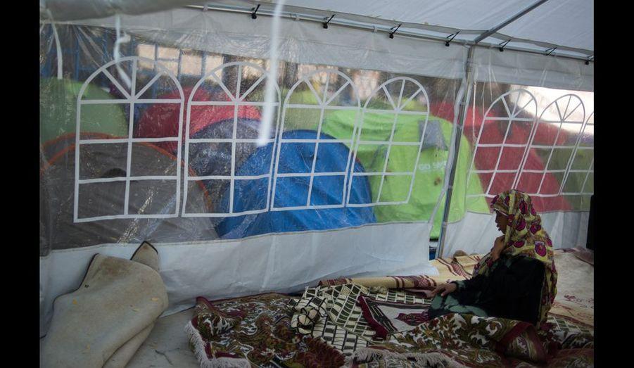 Dans la tente commune transformée en mosquée, une des occupantes fait sa prière. La majorité d'entre eux sont musulmans.