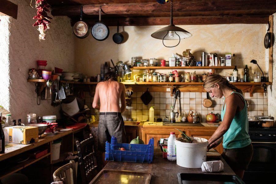 Suzanne met les épluchures dans le seau à compost et Edouard fait la vaisselle.