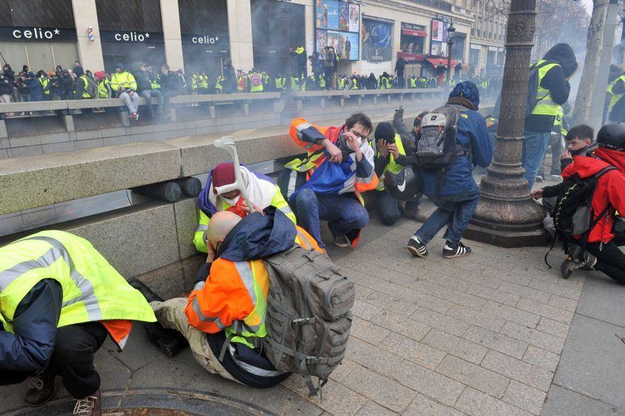 """Des """"gilets jaunes"""" se protègent le visage contre les gaz lacrymogènes à Paris."""