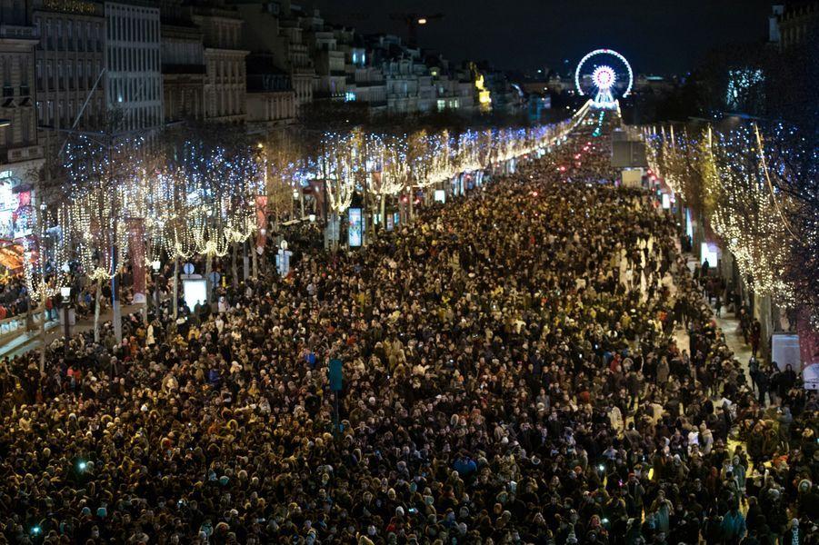 A Paris, plusieurs centaines de milliers de personnes ont bravé le vent et la pluie pour célébrer la nouvelle année.