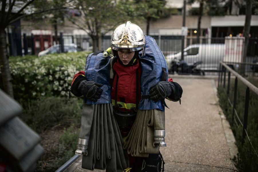 Début de l'intervention, le 17 avril. Chaque tuyau de lance pèse 10 kilos. Cyrielle va les porter jusqu'au 7e étage de l'immeuble où une odeur de gaz a été détectée.