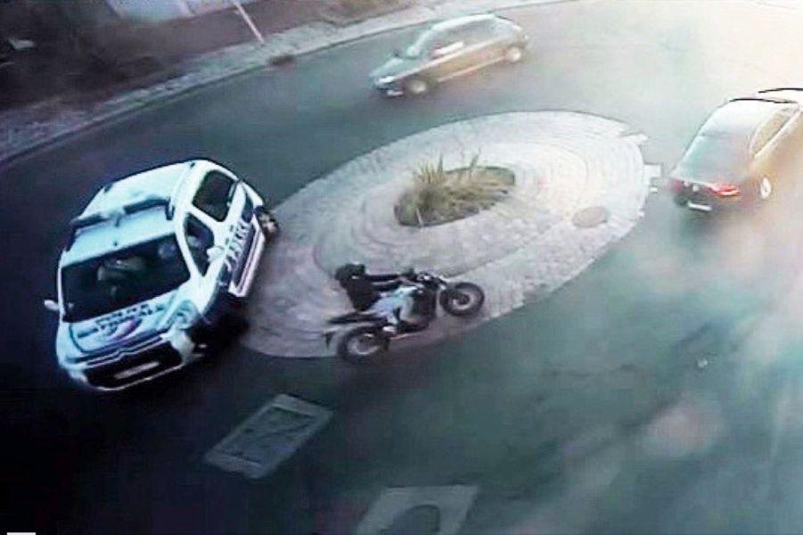 Poursuivi par la police, un « dirty rider » se faufile parmi les automobilistes sur un rond-point.