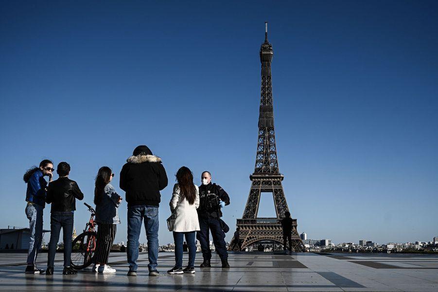 Un policier contrôle des promeneurs, dimanche à Paris.