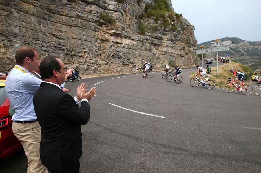 Sur le bord de la route, entreRodez et Mende le 18 juillet 2015, François Hollande, accompagné de Christian Prudhomme,attend le peloton parmi les spectateurs.