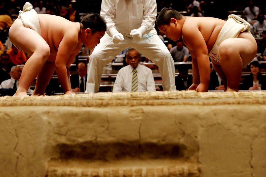 Deux enfants sumotoris préparent leur face à face sur le ring. Le combat commence et se termine par un salut.