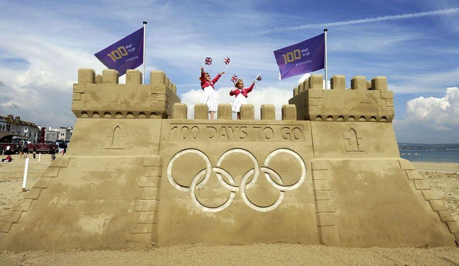 Des enfants se tiennent sur un château de sable construit sur la plage de Weymouth en Angleterre. Cette construction éphémère marque le début des 100 jours avant l'ouverture des Jeux Olympiques de Londres.
