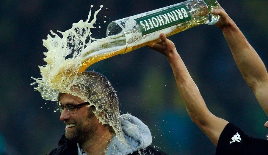 Les joueurs du Borussia Dortmund ont fêté samedi leur deuxième titre de champion d'Allemagne, en renversant de la bière sur la tête de leur coach Juergen Klopp.