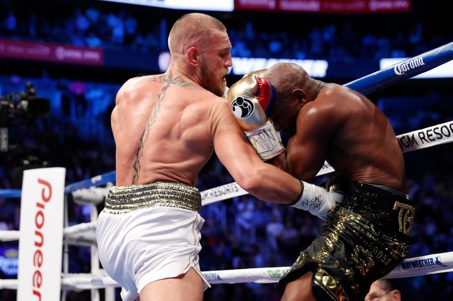 McGregor et Mayweather échangent des coups pendant le combat du siècle à Las Vegas le 27 août 2017.