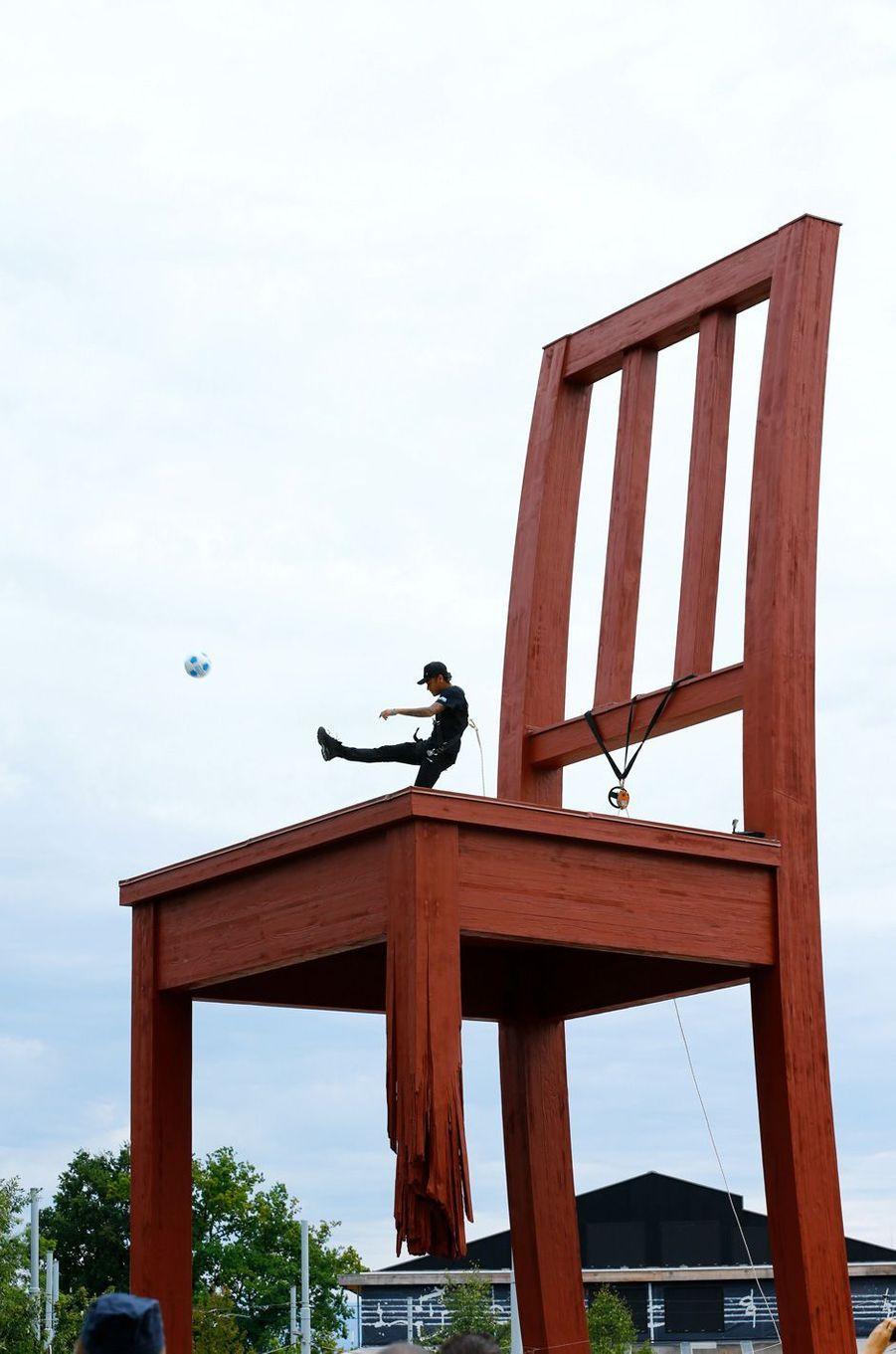 Neymar jonglant avec un ballon sur la «Broken Chair», une immense sculpture représentant une chaise dont l'un des pieds est amputé et érigée sur la place des Nations.