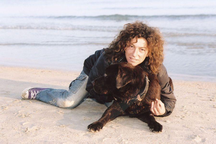 Serrant son chien contre elle, la navigatrice pose allongée dans le sable sur une plage de Marseille.