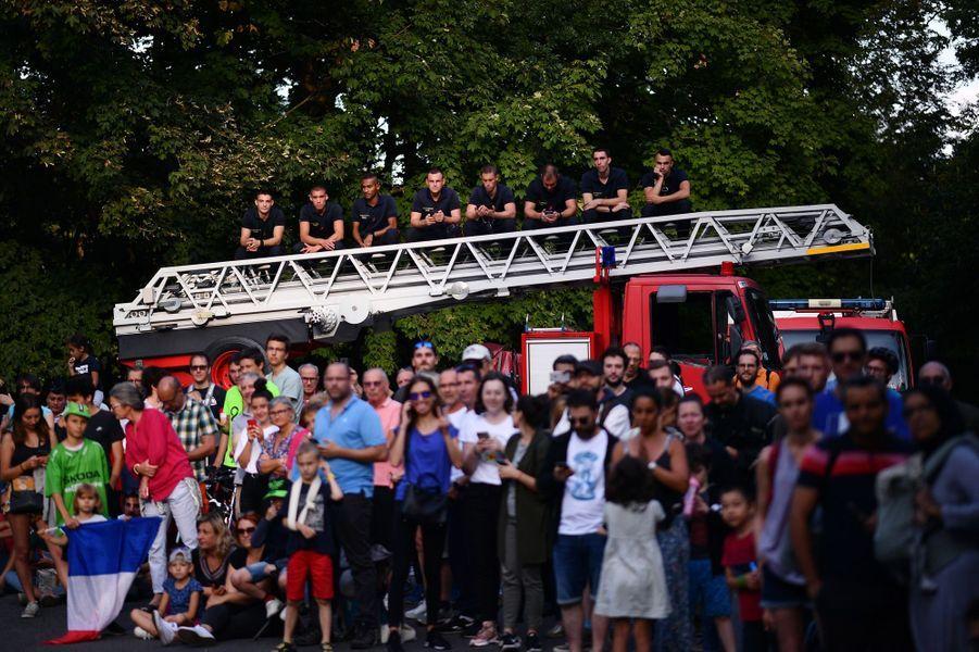 Des pompiers attendent le peloton sur leur échelle lors de la dernière étape entre Rambouillet et les Champs-Elysées, le 28 juillet.