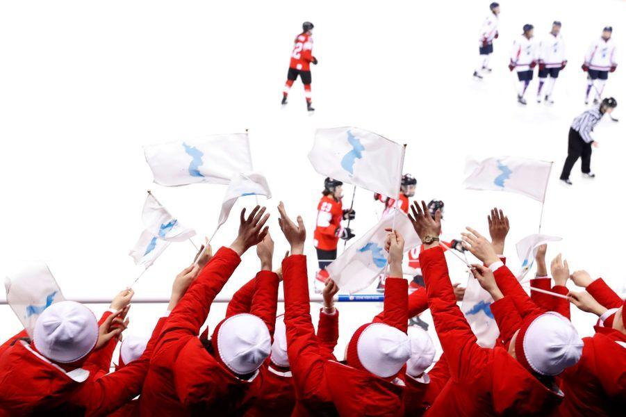 Les supportrices nord-coréennes alignent le drapeau symbole de ces Jeux.