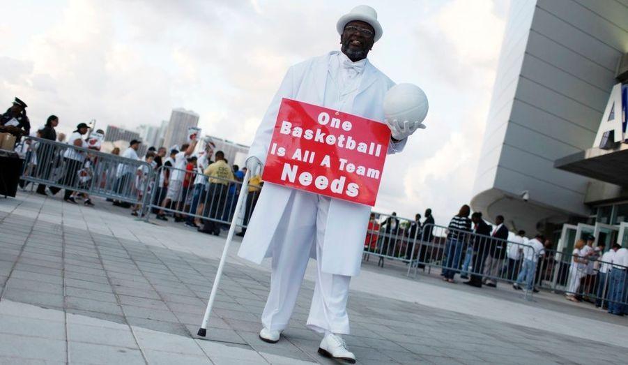 """Un supporter aux couleurs de l'équipe de Miami maintient une pancarte """"Un ballon de basket, c'est tout ce dont a besoin une équipe""""."""