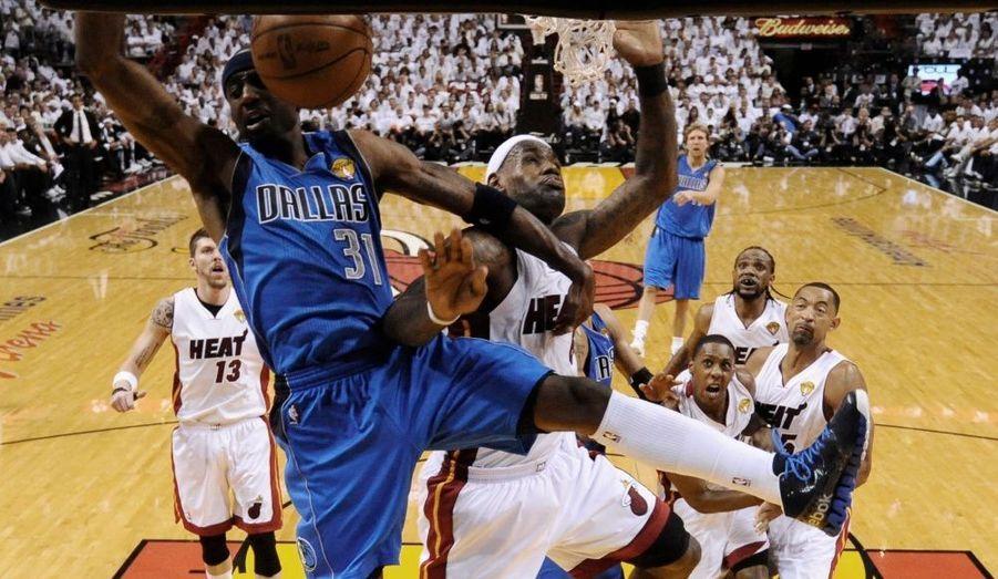 """Aux États-Unis, ça a le même effet médiatique qu'une finale de football en France. A l'exception près que le ballon est orange.Dans la nuit de mardi à mercredi, le premier match de basketball de la finale de NBA a eu lieu en Floride. Il a opposé l'équipe de Miami à celle de Dallas. Bilan: les joueurs communément appelés les """"Heat"""" (Miami) ont pris l'avantage sur les """"Mavericks"""" (Dallas). Il reste au minimum trois matchs en perspective. La première des deux équipes qui remporte quatre victoires sur l'autre est consacrée championne de la NBA. Vêtus d'un maillot blanc: les joueurs de Miami, d'un maillot bleu: ceux de Dallas."""