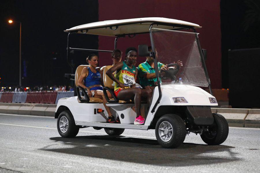 Samedi, des athlètes qui ont abandonné le marathon féminin sont transportées en voiturette de golf.