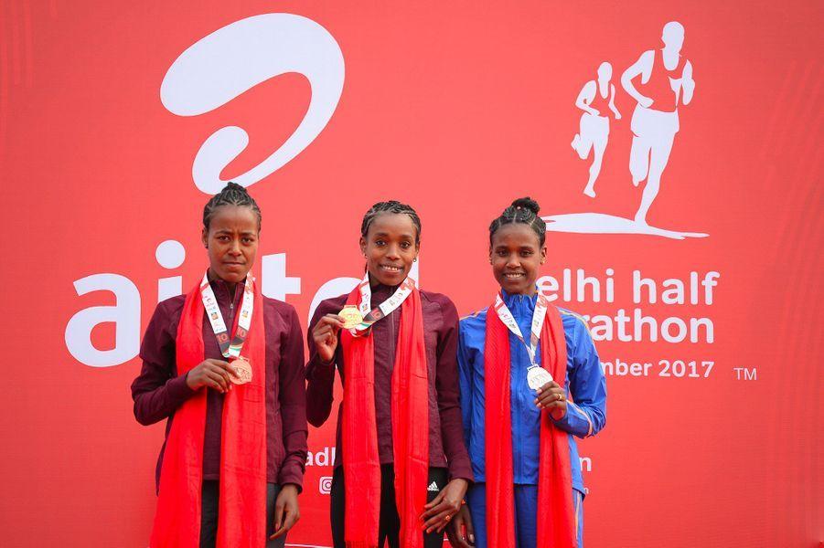 Almaz Ayana(centre) pose avec sa médailled'or aux côtés deAbabel Yeshaneh (droite) etNetsanet Gudeta (gauche).
