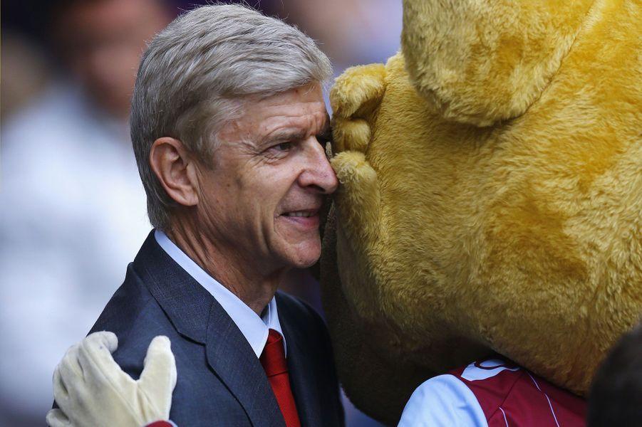 Accolade entre Arsène Wenger, l'entraîneur d'Arsenal et la mascotte d'Aston Villa avant la rencontre entre les deux équipes.