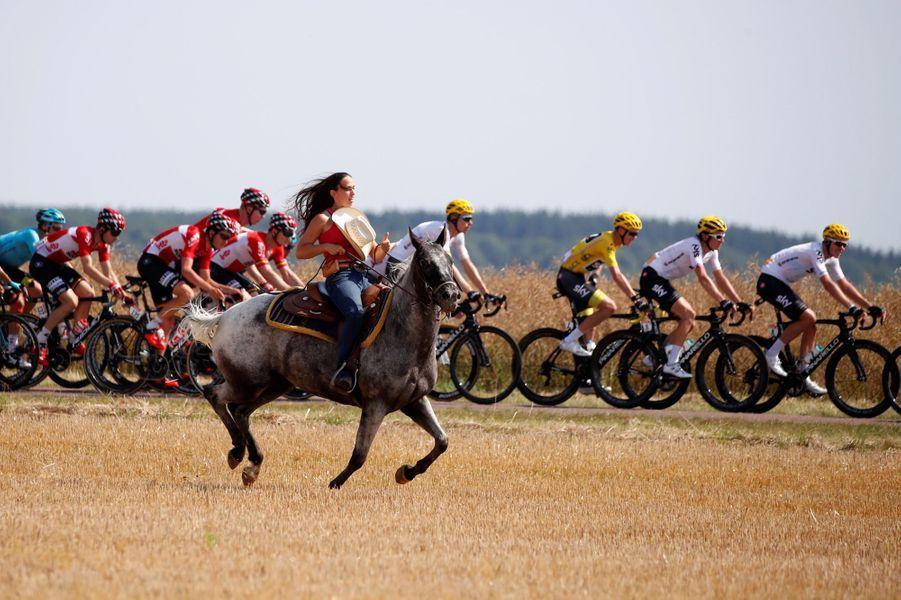 Lors de l'étape entre Vesoul et Troyes, le maillot jauneChris Froome et ses coéquipiers sont escortés par une femme à cheval.