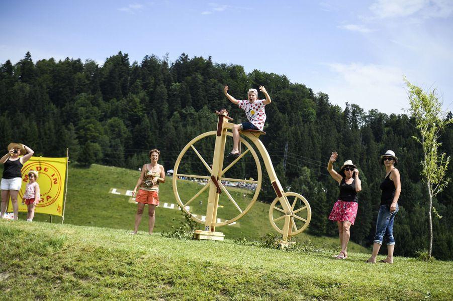 Un enfant sur une sculpture représentant un Grand-bi salue le passage de la Grande Boucle lors de l'étape Dole - Station des Rousses.