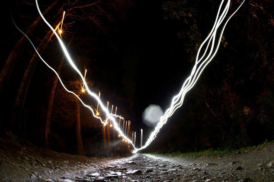 Dans la nuit, les coureurs utilisent des lampes frontales, ici aux Contamines, côté français.