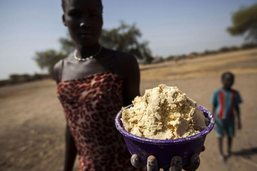 Une jeune femme tient un bol de maïs partiellement bouilli à Ngop au Sud Soudan le 10 mars 2017