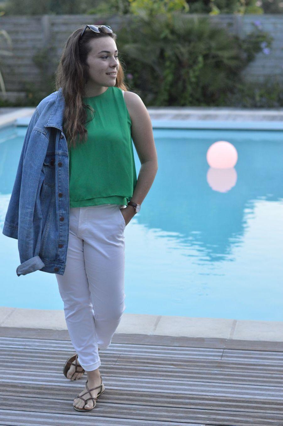 Avec un top vert, un pantalon blanc et des sandales plates : pour un look chic et décontraté