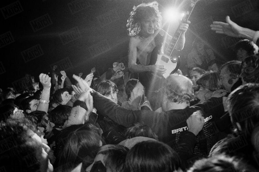 """« Angus Young, le guitariste vedette d'AC/DC, juché sur les épaules de son garde du corps, a entrepris un parcours périlleux au risque de se faire déchiqueter par les """"kids"""" survoltés. » - Paris Match n°1646, 12 décembre 1980"""